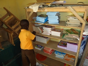 A pupil of Obinyimokyena Primary Searching for textbooks from the school cardboard for his class